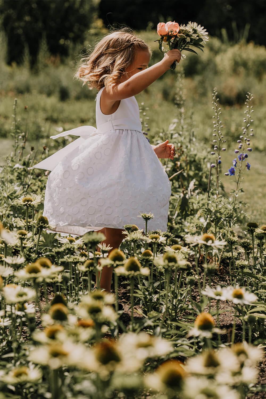 Wedding flower girl spinning in flower garden