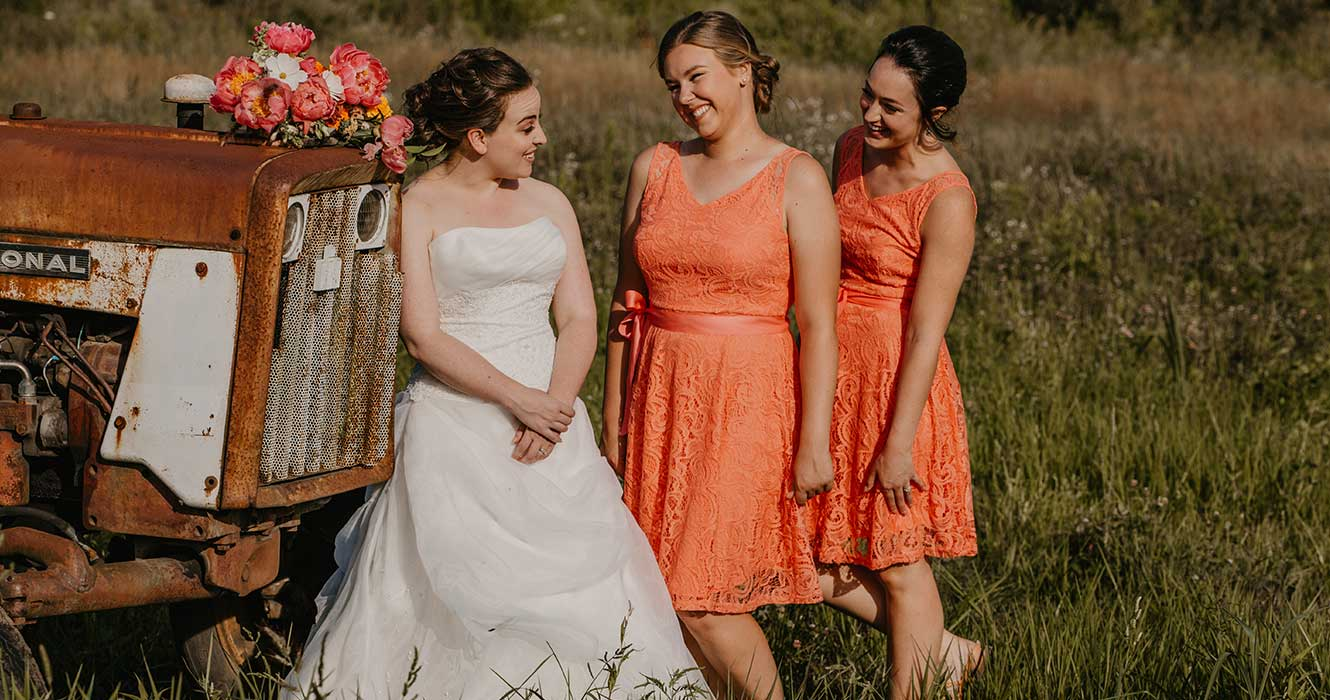 Bridesmaids by rustic tractor at wedding